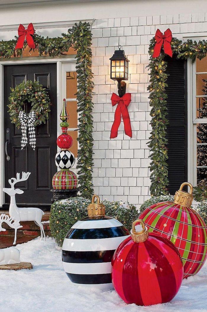 decoration exterieur noel avec des balles enormes devant la maison des guirlandes autour des fenetres et des cerfs decoratifs