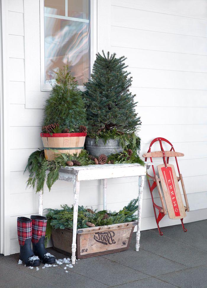 decoration noel exterieur avec des sapins dans des pots a fleurs sur un table devant la maison avec une traîneau a cote