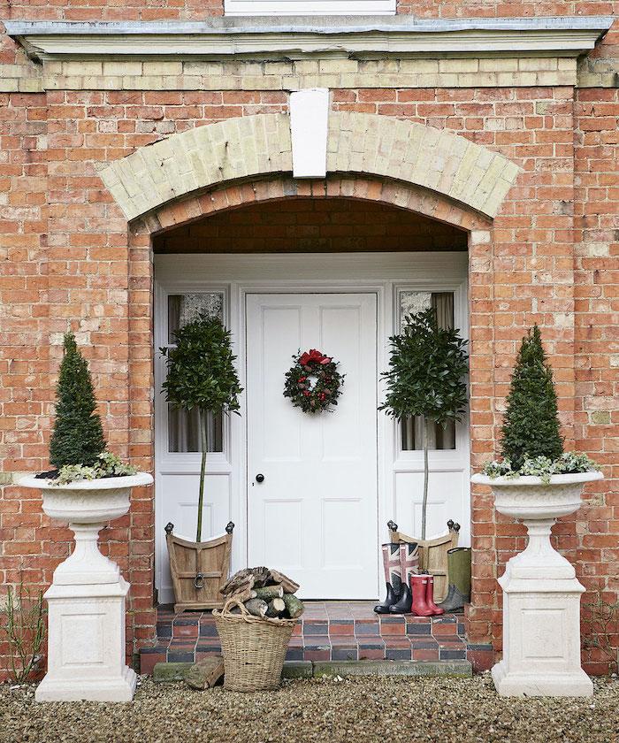 decoration noel exterieure symetrique avec deux arbustes dans des urnes encadrent la porte