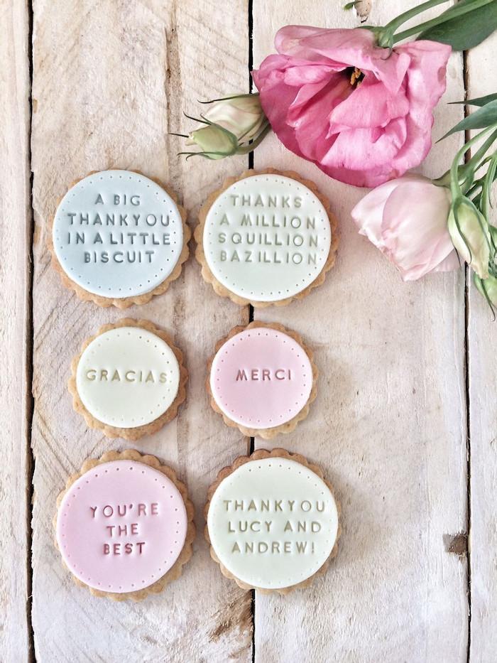 des biscuits personnalisees avec des signatures decores des fleurs sur une table en bois liste cadeau d anniversaire