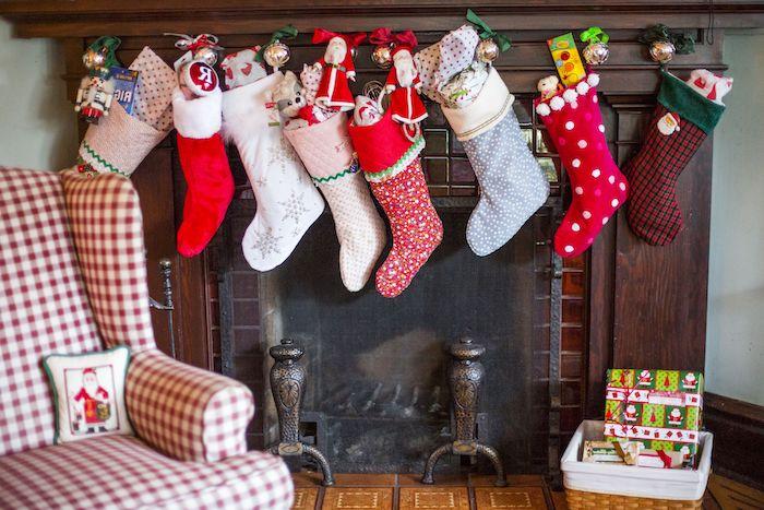 des cahussettes suspendus de la cheminée pleines avec des cadeaux une fauteuil en carreaux a cote