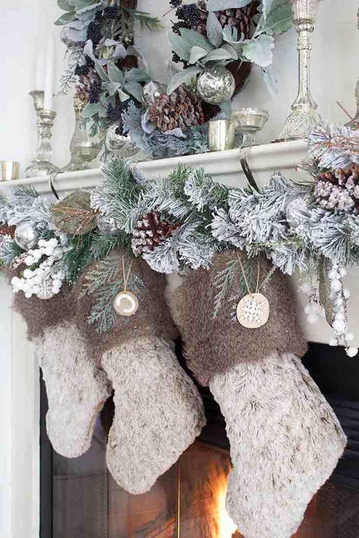 des chausettes tricotees suspendus de la cheminée avec des guirlandes et des cones de pin saupodres de fausse neige