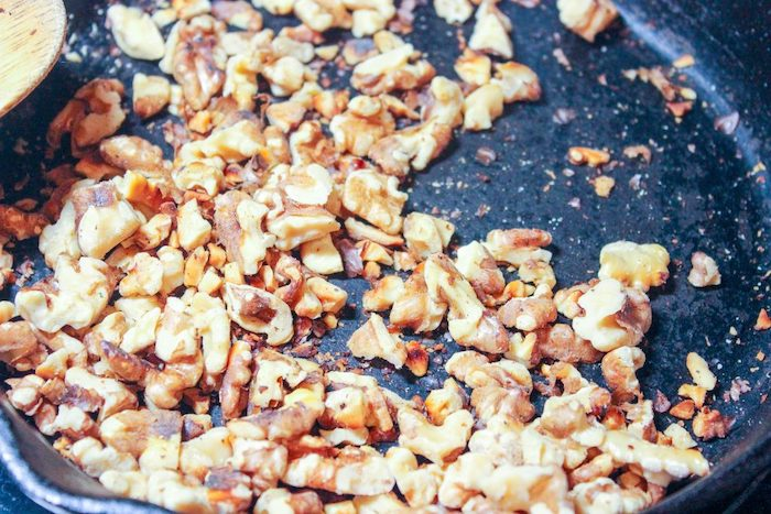 des noix dans une poele portees au feu pour une recette salade d hiver