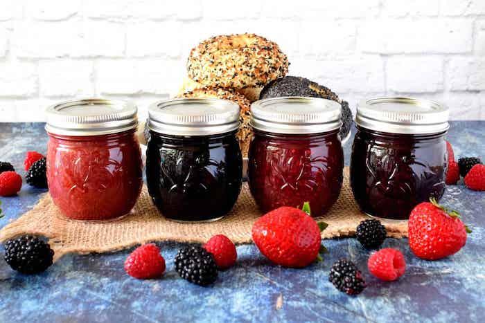 des pots a confiture de fraises myrtilles et framboises devant deux pains idée cadeau d anniversaire