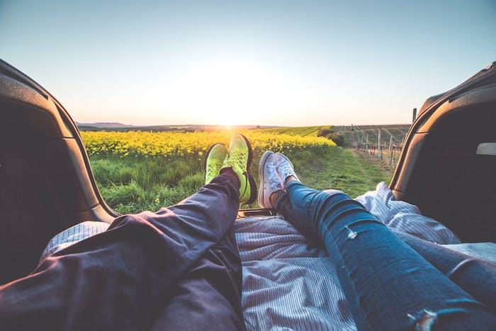 deux personnes assises dans un coffre de voitre regardent le soleil qui se couche