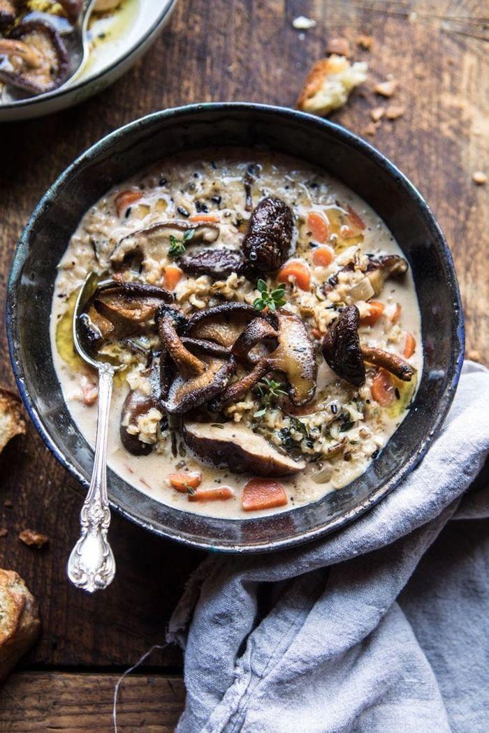 entree chaude avec des champignons et des legumes avec une cuillere argenitne