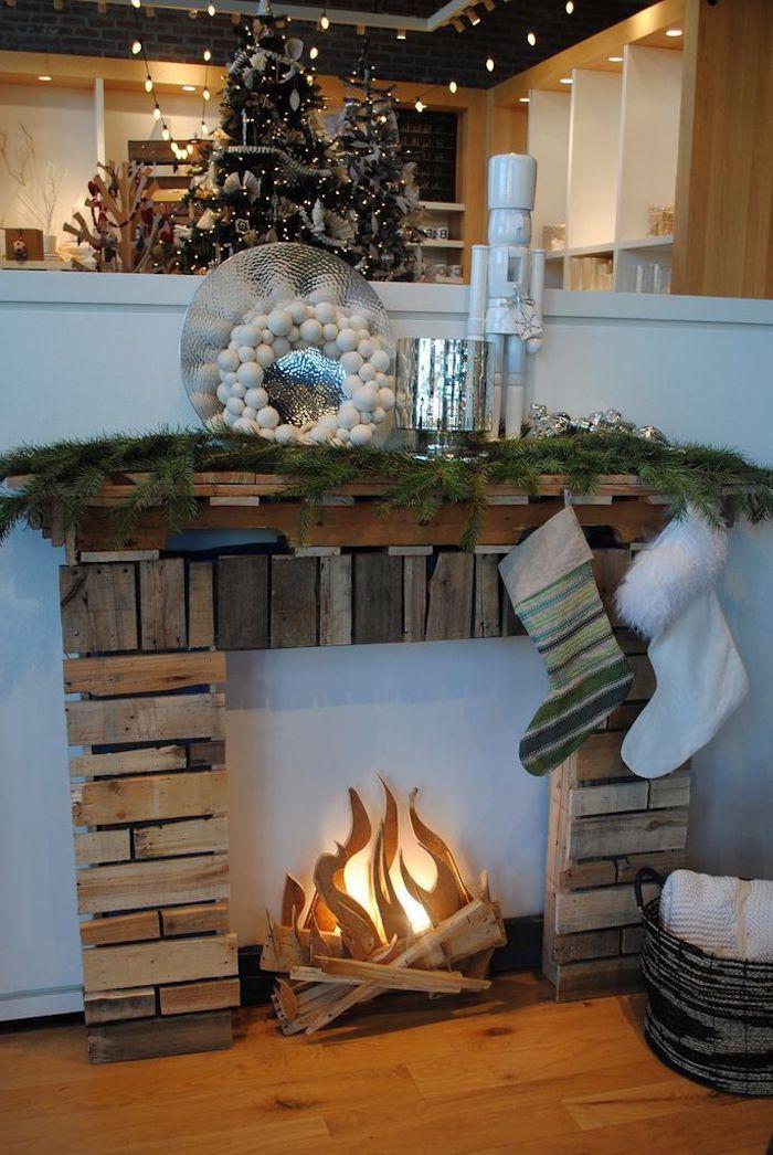 fausse cheminée noel avec des morceaux de bois decoree avec des chaussettes branches de sapin et une couronne en boules de fausse neige