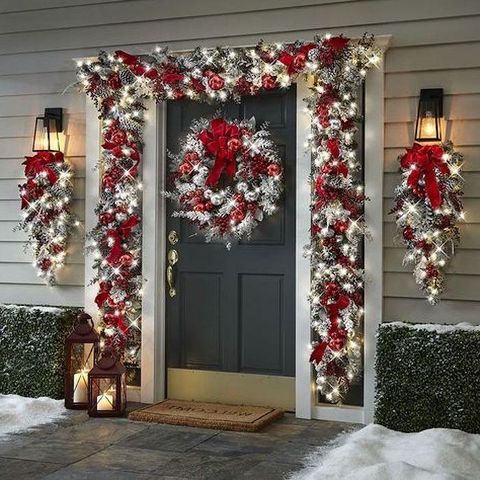 guirlande lumineuse exterieur noel avec des balles rouges et argenitnes combines avec des rubans deux lanternes devant la porte