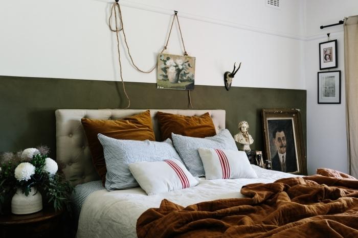 idée peinture chambre adulte bicolore peinture vert foncé table de chevet bois foncé cadres photos portrait statuette cornes décoratives