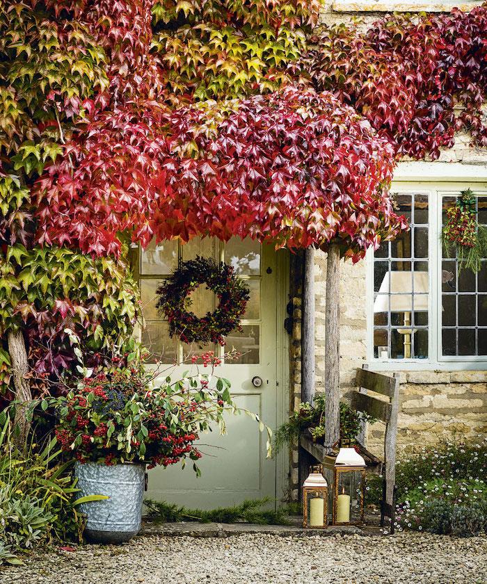 idee deco noel exterieur naturel avec des arbres une courrone a la porte et chaise en bois devant la maison