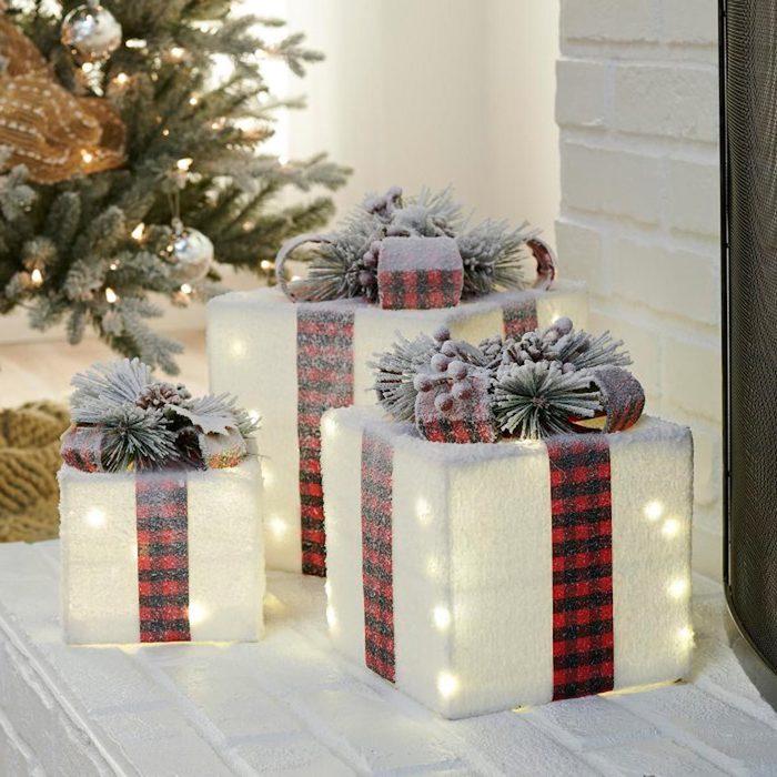 idee originale de decoration avec une fausse neige et des cadeaux decoratives devant la porte pres d un sapin lumineux
