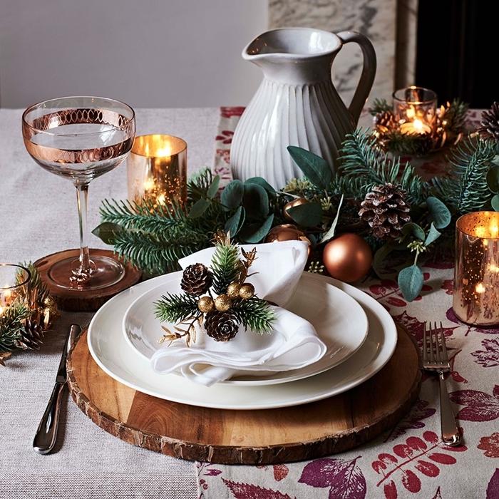 les plus belles tables de noel rondelle bois assiette blanche serviette verdure pommes de pin verres accents rose gold