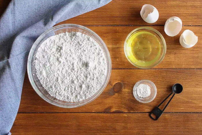 les produits pour un glaçage des oeufs pasteurises un bol de sucre de confeterie avec une nappe sur la table en bois