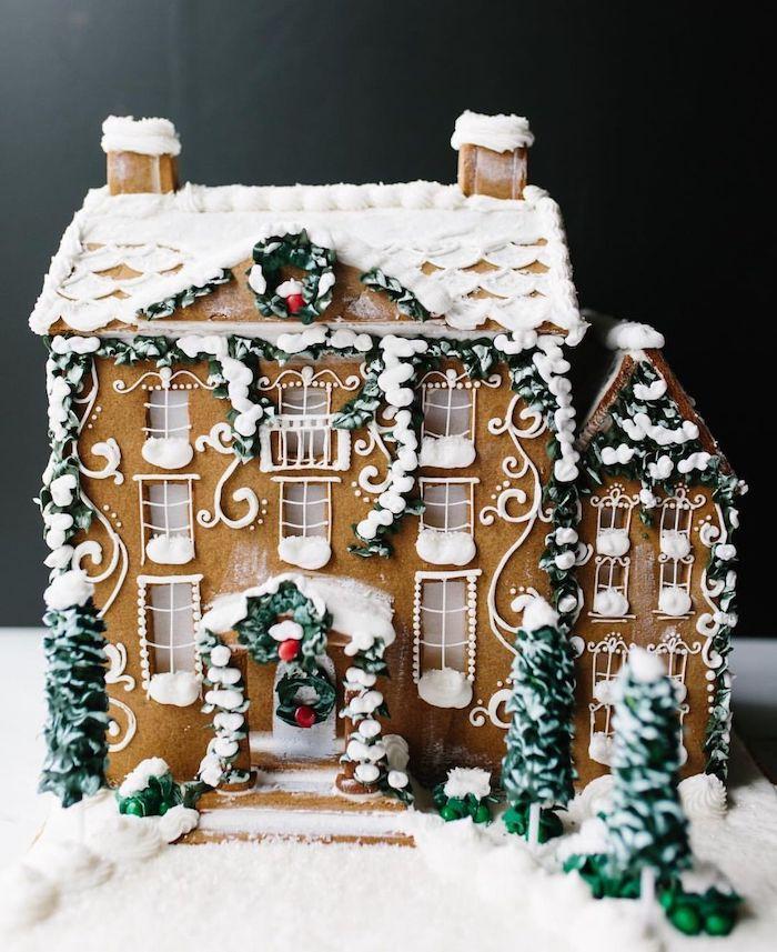 maison en pain d épices décorée avec de glaçage et des figurines vertes comestibles idee de dessert