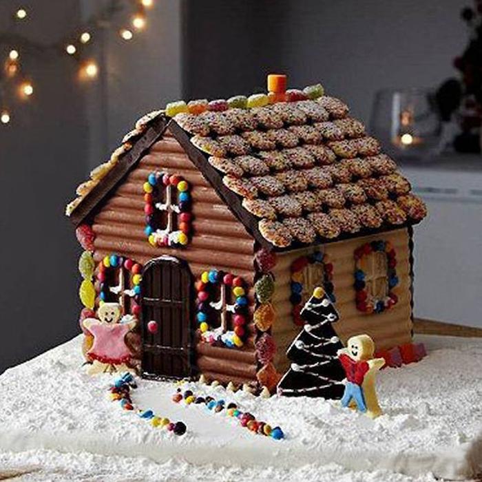 maison en pain d épices décorée avec des petits bonhommes devant la porte et des bonbons gelees sur le toit