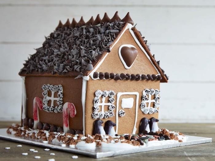 maison en pain d epices decoree avec des elements en chocolat et des batons gelees