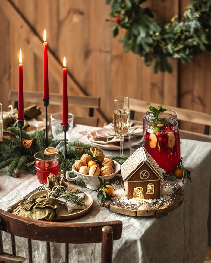 maison noel gingembre table de noel traditionnelle assiette ronde bambou bougies rouges centre table branches sapin