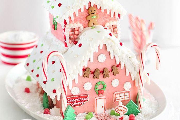 maison pain d épices pour des enfants en couleurs rose et blanc décoree avec des bonhommes et des batons sucrés