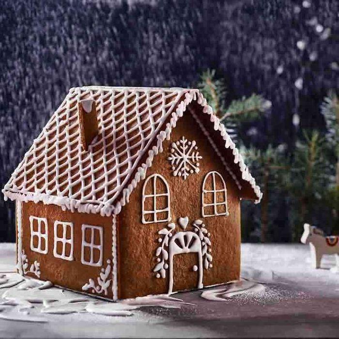 maison pain d epice en forme traditionnellle decoree avec de glacage royal et des ornaments hivernales