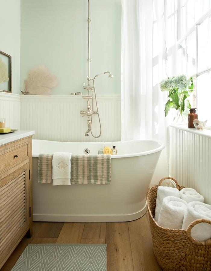 modele salle de bain rétro style peinture murale pastel vert menthe baignoire blanche panier tressé serviette de bain