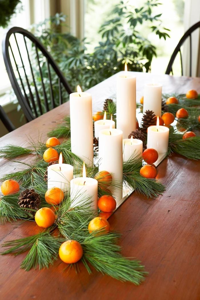 oranges pommes de pin centre de table noel a faire soi meme bougies blanches branches arbre de noel vertes