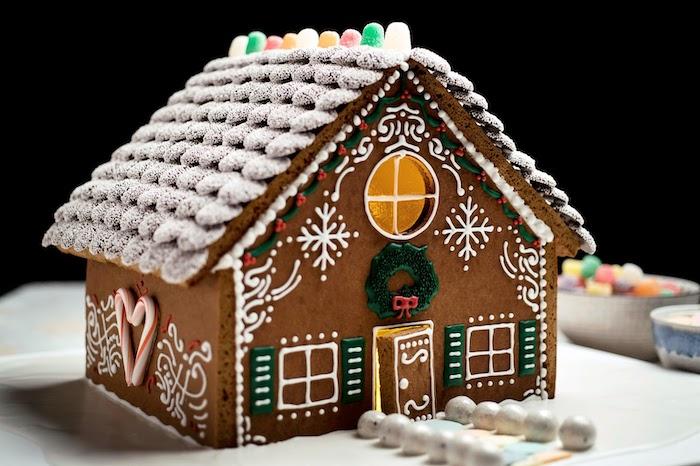 pain d epice maison decoree avec des perles comestibles glacage coloree et des petits bonbons sur le toit
