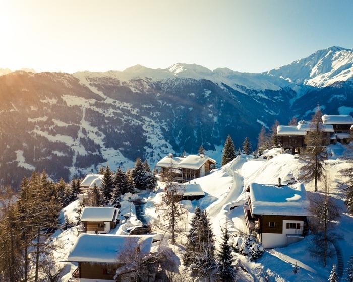paysage montagne hiver rayons soleil sommets montagne enneigée village maison bois toit neige