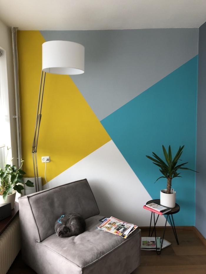 peinture géométrique mur salon décoration coin lecture fauteuil gris table ronde café noire plantes vertes lampe blanche