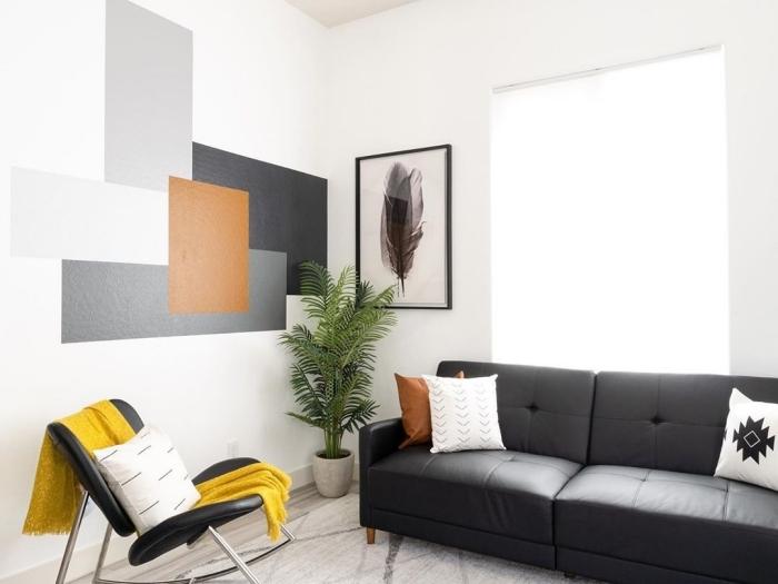 peinture géométrique salon décoration moderne aménagement salon canapé boutonné noir coussin blanc chaise noir jeté jaune