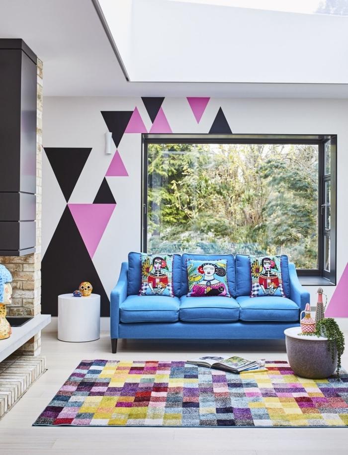 peinture géométrique salon tapis motifs carreaux multicolore canapé bleu table café béton formes triangulaires peinture rose
