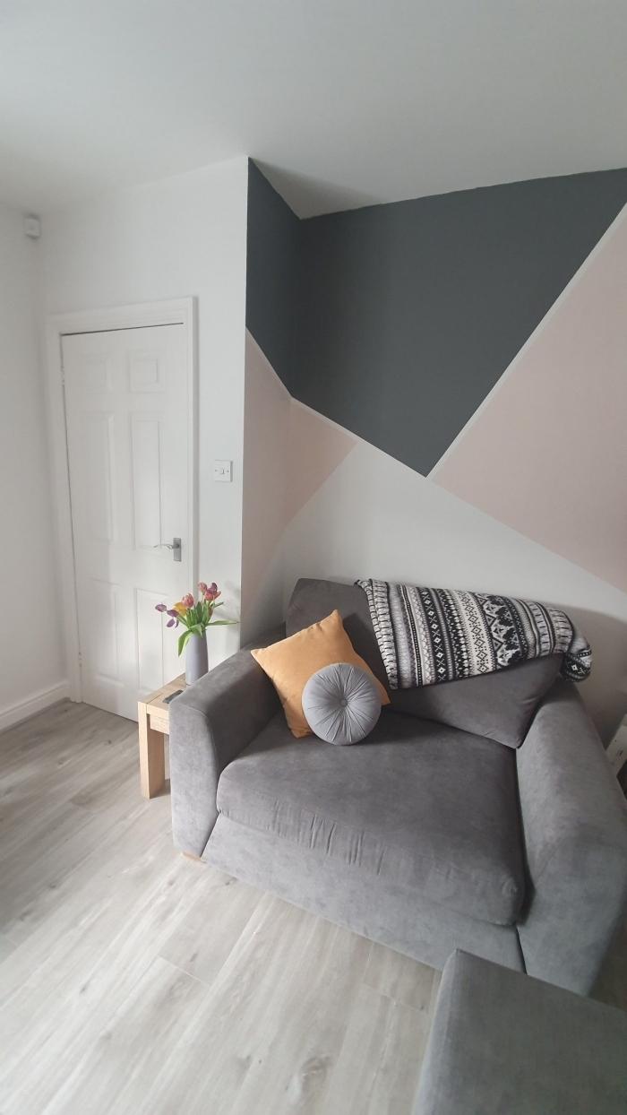 peinture mur triangle fauteuil gris anthracite jeté motifs barbère blanc et noir coussin orange pastel table bois basse