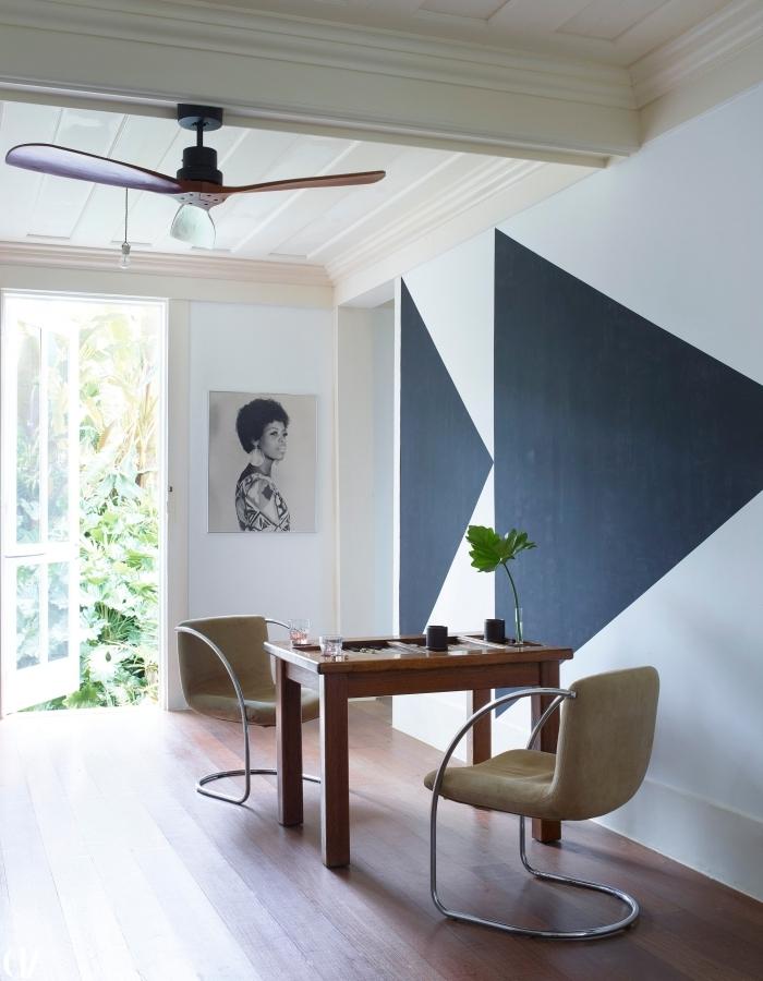 peinture murale géométrique triangles gris anthracite sur fond blanc table bois foncé chaise velours métal portrait blanc et noir