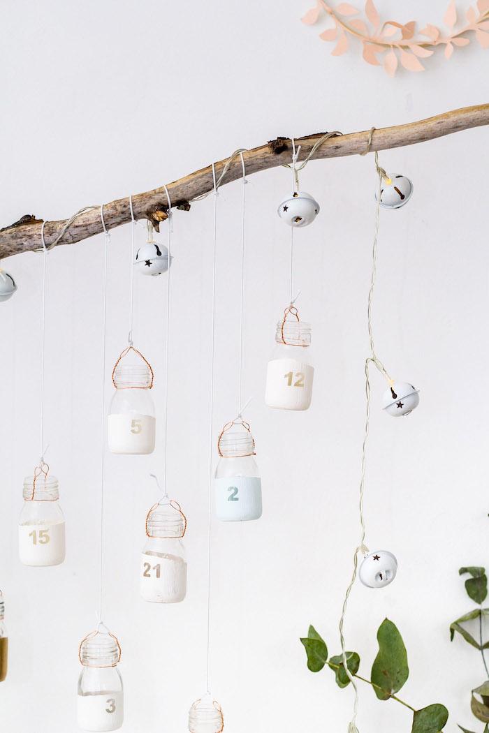 petites fioles flacons de verre repeints et dotés de chiffres suspendus sur une branche calendrier de l avent fait maison