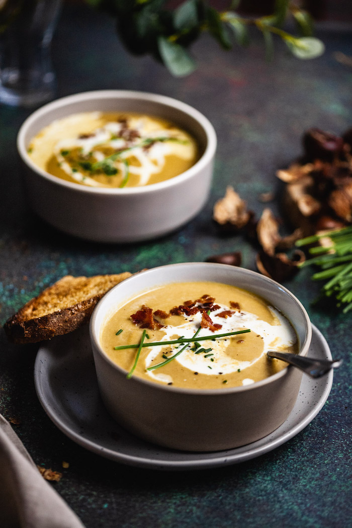 recette entree originale une soupe creme avec des flocons de poivron deux assiettes gris et une tranche du pain
