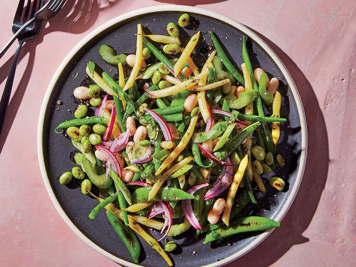 recette salade composee avec des cereales et de l oignon rouge servie dans assiette noire sur nappe rose