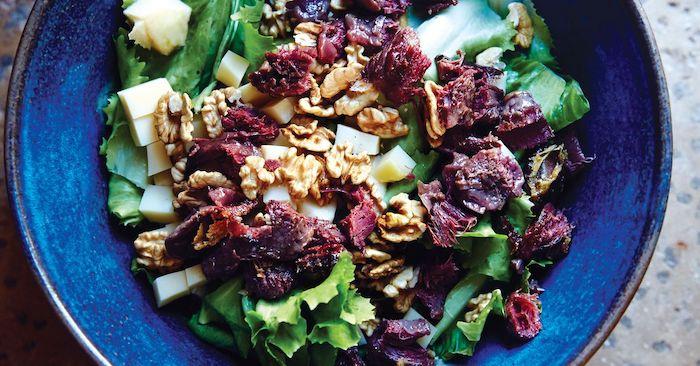 salade a la base des legumes vertes avec des tomates seches et des noix dans une assiette ceramique bleue