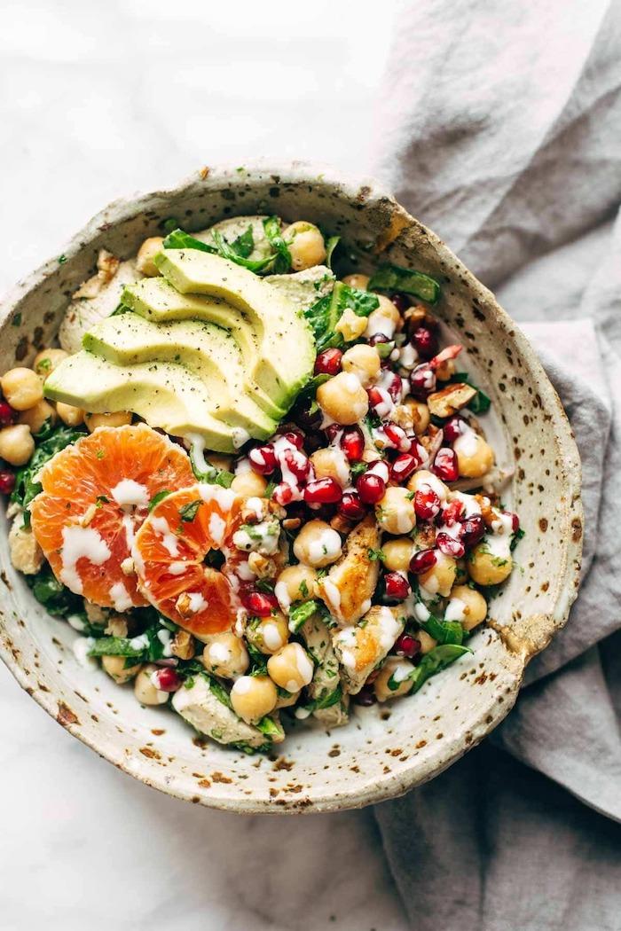 salade avocat crevette avec pois de chiche servie dans un bol de pain arabe sur une nappe gris