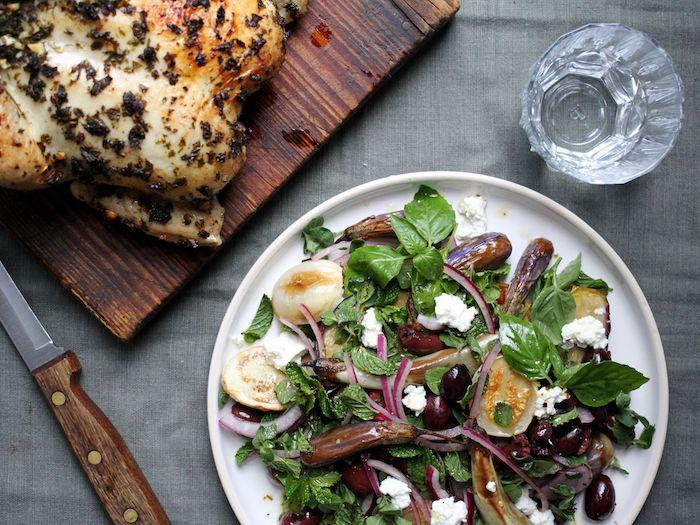 salade composée comme garniture avec un poulet aux herbes roti servi sur un plateau en bois