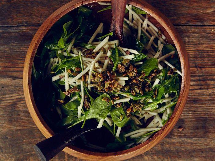 salade de saison avec des epinards des germes et raisins avec deux cuilleres et un bol en bois