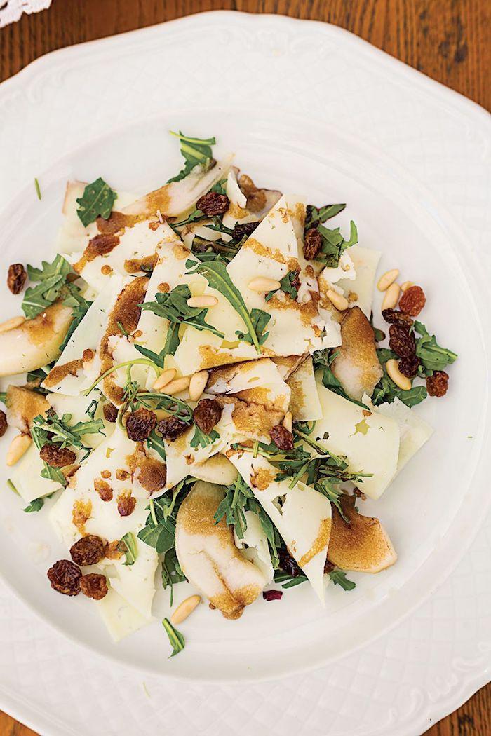 salade de saison de la roquette avec de morecaux de poire et des raisins dans une assiette blanche