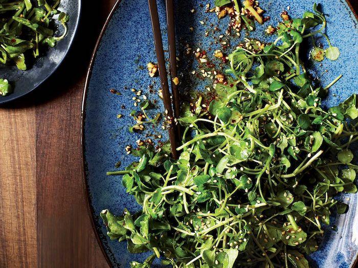 salade exotique avec des germes et des noix ecrases servie dans une assiette luxeuse avec des baguettes