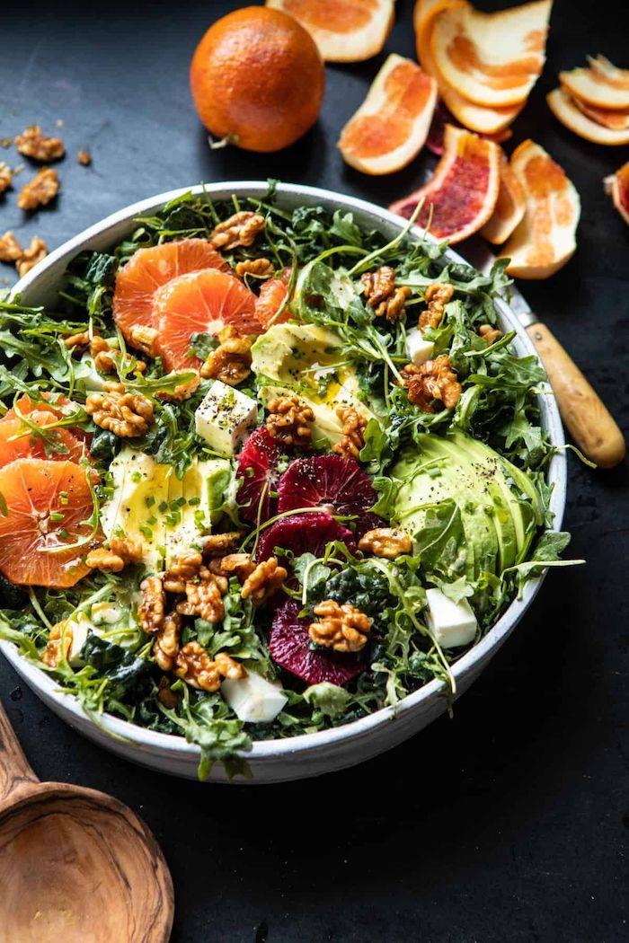 salade verte garni avec des noix et un avocat tranche des clementines pelees a cote d une assiette bleue