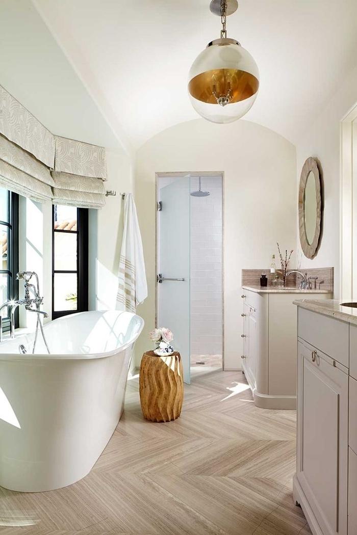 salle de bain avec baignoire autportante luminaire laiton meubles bois revêtement sol aspect bois clair