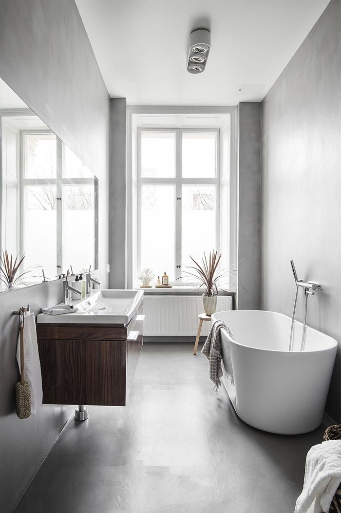salle de bain avec baignoire blanche autoportante robinet inox table basse cbois plante éclairage spots led