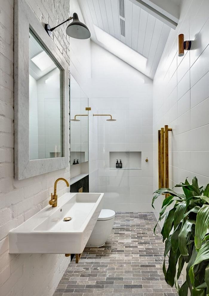 salle de bain moderne petit espace carrelage blanc fenêtre toit mur briques blanches miroir plantes vertes intérieur