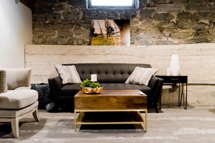 salle de sejour style moderne murs en pierres canapé en gris anthracite table basse