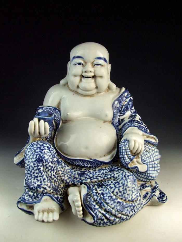 statue de bouddha sourriant avec un ventre gonfle et torse nu
