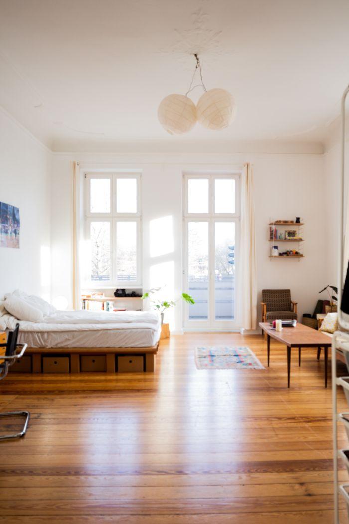 studio appartement ensoleille sol en parquet clair murs blancs plafond haut