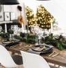 table bois rustique couvercles dorés centre de table branches de sapin bougies blanches pommes de pin assiettes noires