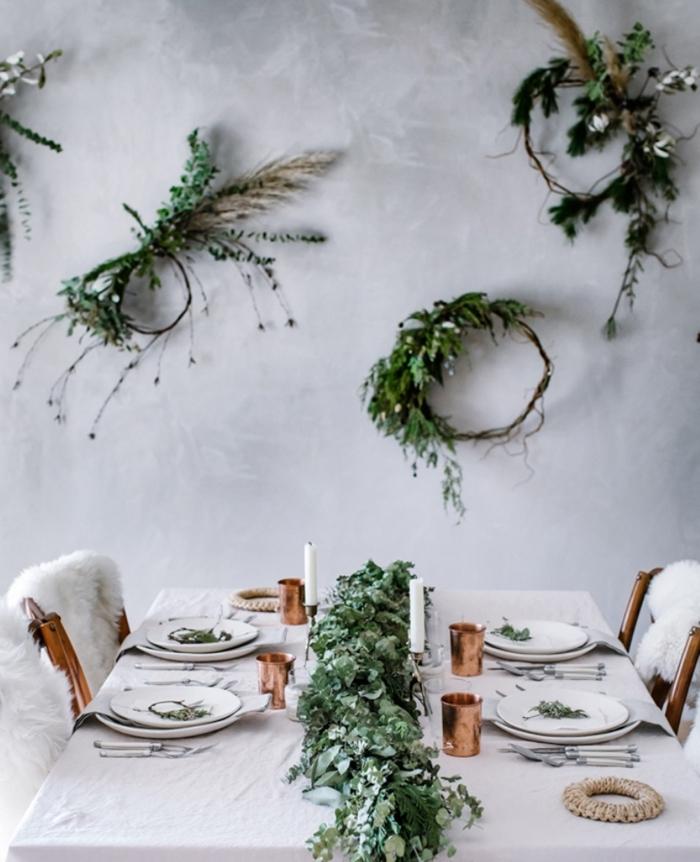 table de noel décoration naturelle nappe blanche centre de table en branches et feuilles vertes couvercle cuivre